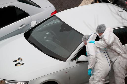 Forensics officers examine a silver Audi with bullet holes in its windscreen at the scene near junction 24 in Huddersfield