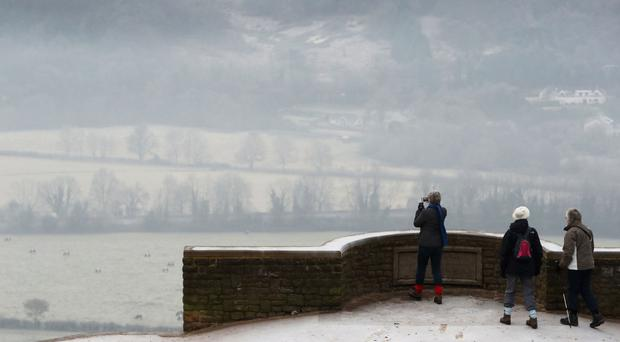 Walkers photograph the mist from Box Hill in Surrey
