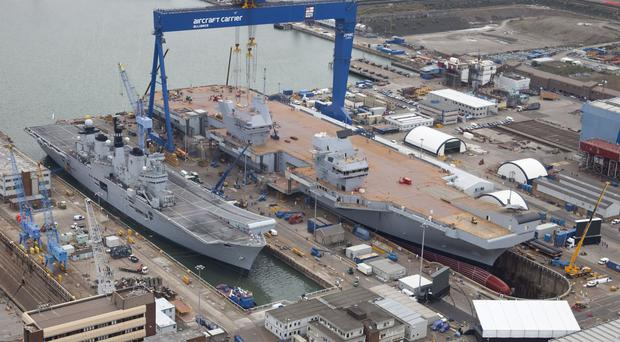 The Royal Navy's new aircraft carrier HMS Queen Elizabeth (right) at Rosyth dockyard