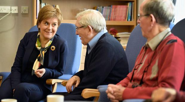 First Minister Nicola Sturgeon speaks with Jimmy King and Jim Langley during a visit to Midlothian Community Hospital in Bonnyrigg