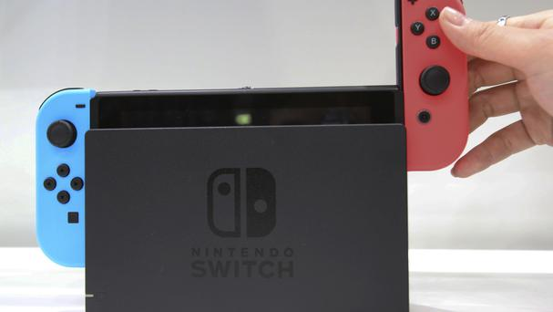 A model puts the controller on to the Nintendo Switch during a presentation event of the new Nintendo Switch in Tokyo. (AP Photo/Koji Sasahara)