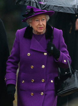 The Queen arrives in the rain for a church service at Flitcham in Norfolk