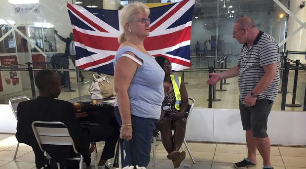 British tourists check in at Banjul Airport, Gambia, for special flights after the threat of a regional military intervention loomed (AP Photo)