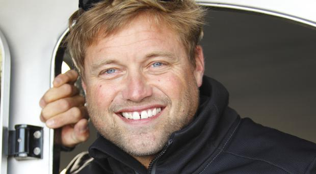 British sailor Alex Thomson crossed the finish line off Les Sables d'Olonne on the French Atlantic coast on Friday morning