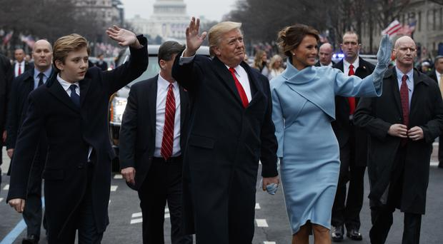 Donald Trump and first lady Melania Trump walk along the Inauguration Day parade route after being sworn in as the 45th President of the United States (AP Photo/Evan Vucci, Pool)