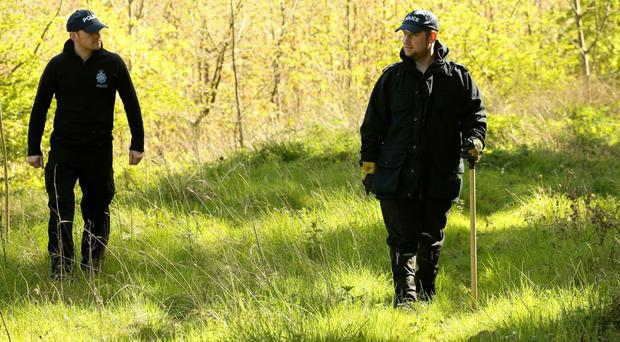 Police officers search a wooded area at Royston Heath after children's author Helen Bailey was reported missing