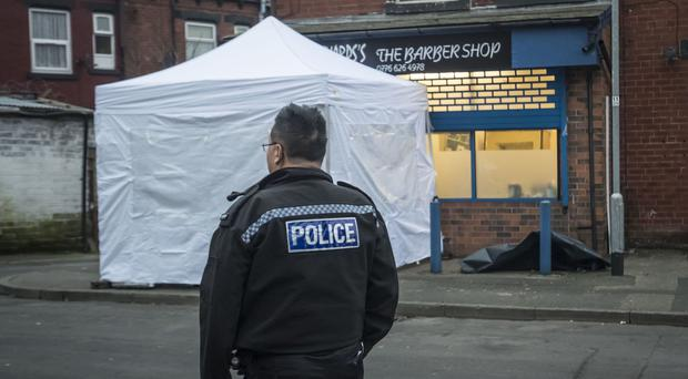 Police at the scene in the Harehills area of Leeds where a man was shot dead.