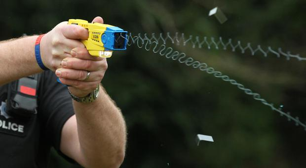 A police officer demonstrating the use of a Taser
