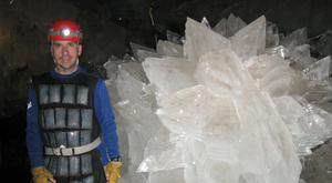 Mario Corsalini by giant gypsum rosette crystals in the Naica mine in Chihuahua, where an extraordinary population of microbes has been discovered trapped in crystal (New Mexico Institute of Mining and Technology/PA)