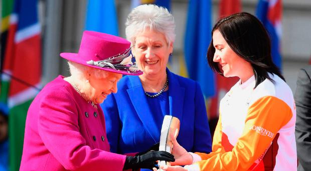 The Queen passes the Commonwealth Games baton to its first bearer, Australian cyclist Anna Meares, at a ceremony at Buckingham palace also attended by Jessica Ennis-Hill