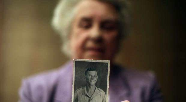 Alma Williams holds a photograph of her late brother Lance Corporal (LCpl) Ronald George Blackham