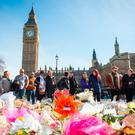 People view floral tributes at the scene