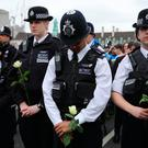 Police officers lay flowers during a vigil on Westminster Bridge in central London