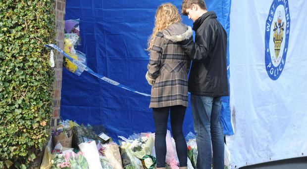 Lydia Wilkinson, the daughter of stabbing victims Peter and Tracey Wilkinson, views floral tributes with her boyfriend at her family home in Stourbridge