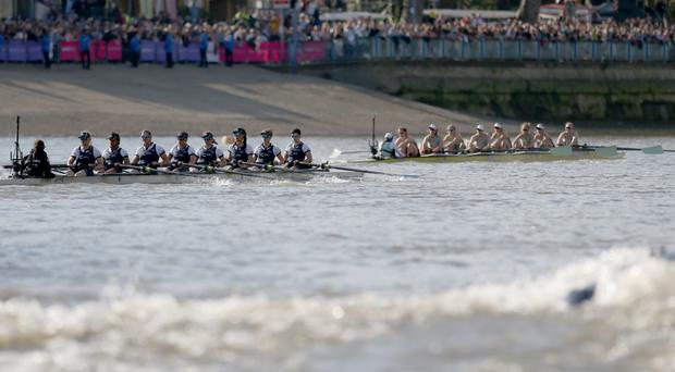 The Cambridge women's crew (right) lead the Oxford women's crew (left) during the Boat Race