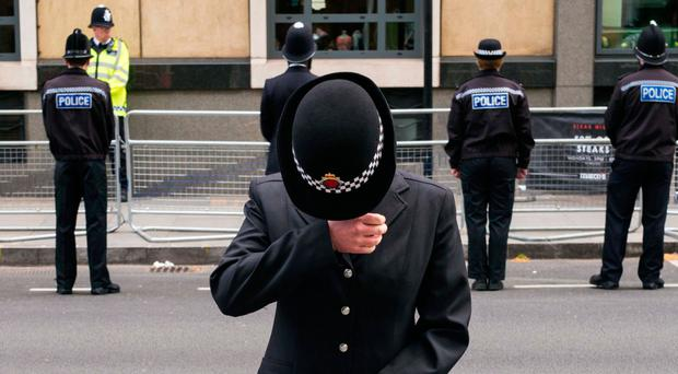A police officer wipes away tears as she and colleagues line the route of the funeral cortege of PC Keith Palmer in London