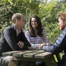 The Duke and Duchess of Cambridge and Prince Harry in conversation at Kensington Palace, London