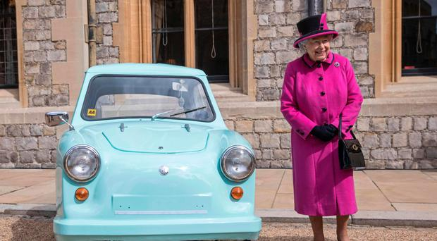 The Queen stands next to a classic Invacar invalid carriage during a ceremony at Windsor Castle to celebrate the 40th anniversary of Motability
