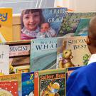 A child looks at books (John Stillwell/PA)