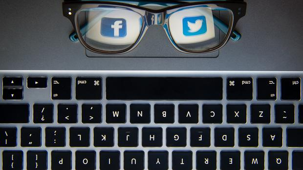 The logos of social network sites Facebook and Twitter reflected in a pair of glasses