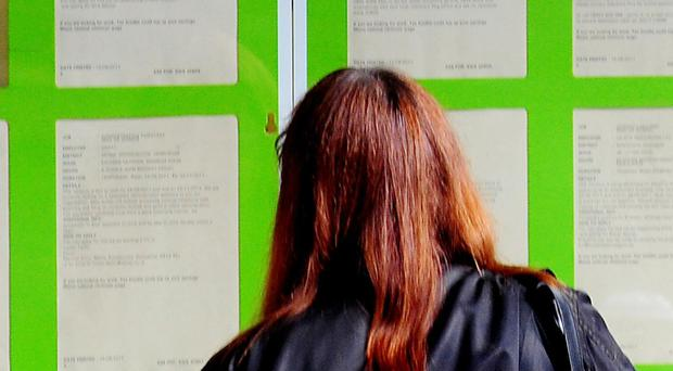 A woman looking into the window of a job centre (Rui Vieira/PA)
