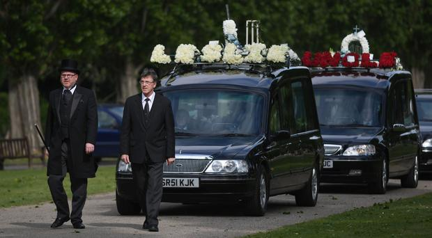 A hearse carrying the coffin of Leslie Rhodes arrives at North East Surrey Crematorium in Morden
