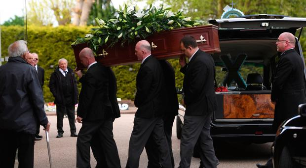 The coffin of Leslie Rhodes is carried into North East Surrey Crematorium