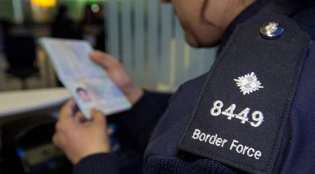 Border officer checking passports (Steve Parsons/PA)