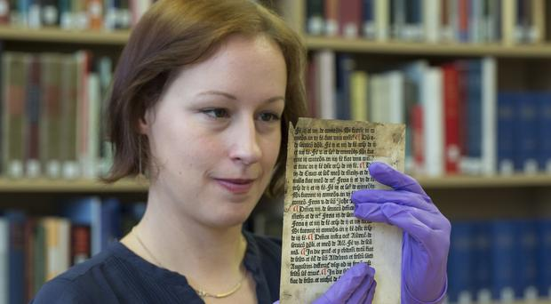 Erika Delbecque holding one of two pages of a 15th century printed text by English printer William Caxton which have been unearthed at the university (University of Reading/PA)