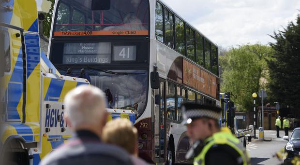 Police at the scene as a bus is towed away (John Linton/PA)