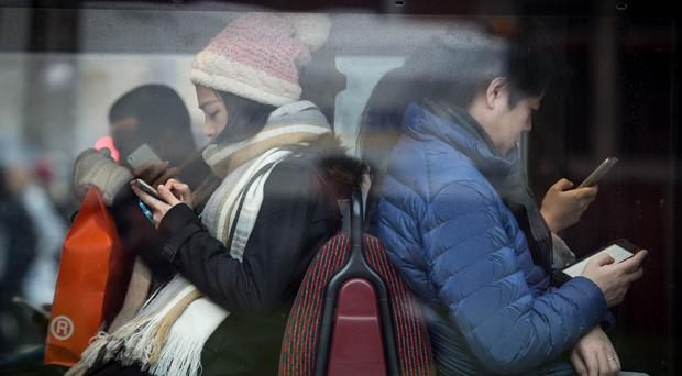 Young people using smartphones (Stefan Rousseau/PA)