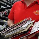 A Royal Mail worker sorts post (Andrew Milligan/PA)