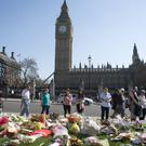 Floral tributes in Parliament Square outside the Palace of Westminster ( Isabel Infantes/PA)