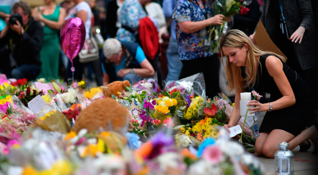 People lay flowers in St Ann's Square after relocating them from Albert Square in Manchester, northwest England on May 24, 2017, placed in tribute to the victims of the May 22 terror attack at the Manchester Arena.