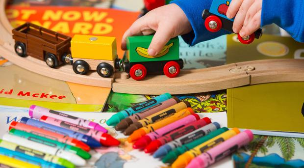 A child plays with toys (Dominic Lipinski/PA)
