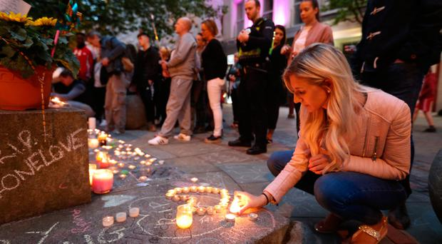Mourners view tributes in St Ann's Square, Manchester, as they prepare to mark the passing of exactly a week since the Manchester Arena terror attack