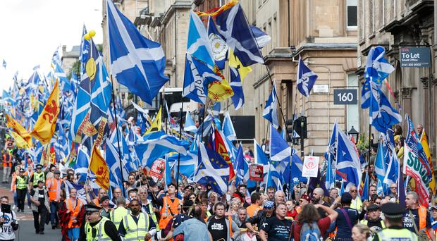 People taking part in the March for Independence wave Saltires in Glasgow city centre (Robert Perry/PA)