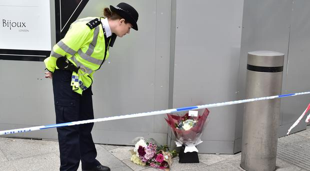 A police officer looks at flowers left on St Thomas Street, London (Dominic Lipinski/PA)