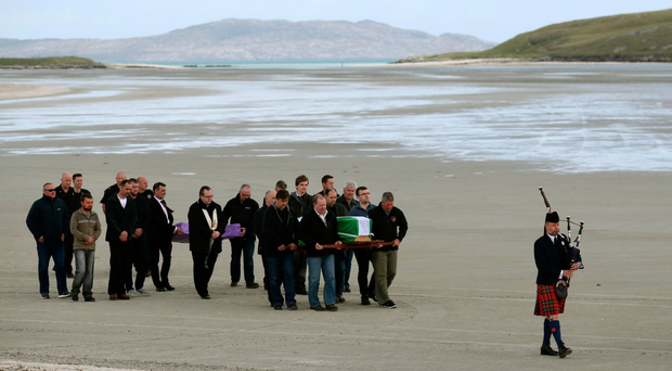 The coffin of Eilidh MacLeod draped in the Barra flag is carried across Traigh Mhor beach at Barra airport after it arrived by chartered plane yesterday