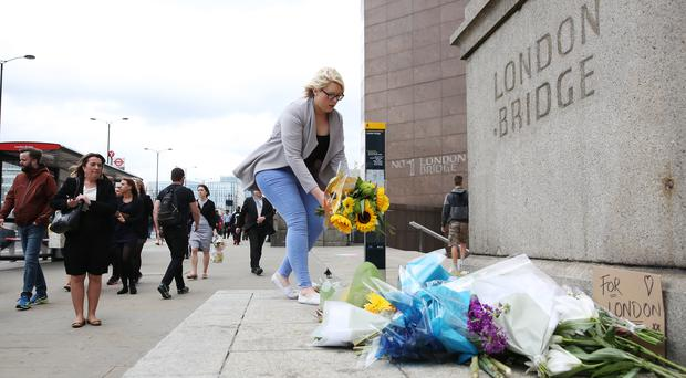People lay flowers near London Bridge following Saturday's terrorist attack (Isabel Infantes/PA)