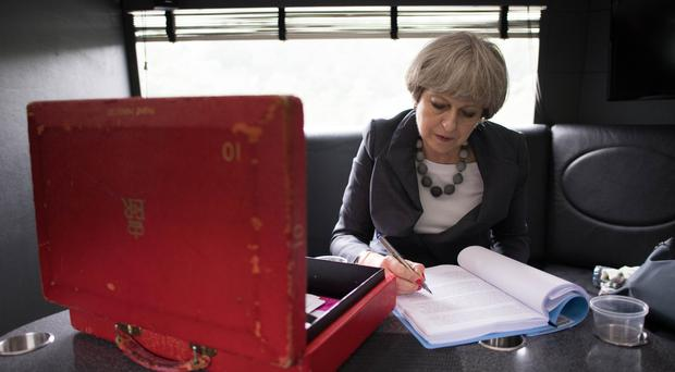 Theresa May works on her campaign bus during a tour of Britain (Stefan Rousseau/PA)