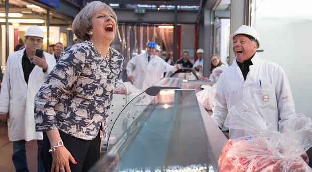 Theresa May laughs during a visit to Smithfield Market (Stefan Rousseau/PA)