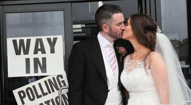 Alliance candidate for West Belfast Sorcha Eastwood casts her vote in the 2017 General Election, with her husband, Dale Shirlow, at a polling station in Lisburn, Northern Ireland, still wearing her wedding dress after they were married earlier in the day (Brian Lawless/PA)