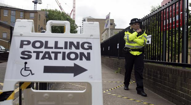 A police officer outside a polling station (Victoria Jones/PA)