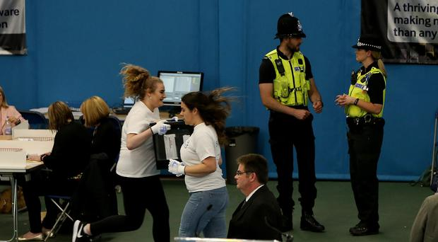 Staff run with ballot boxes as the General Election count gets under way in Sunderland (Nigel Roddis/PA)