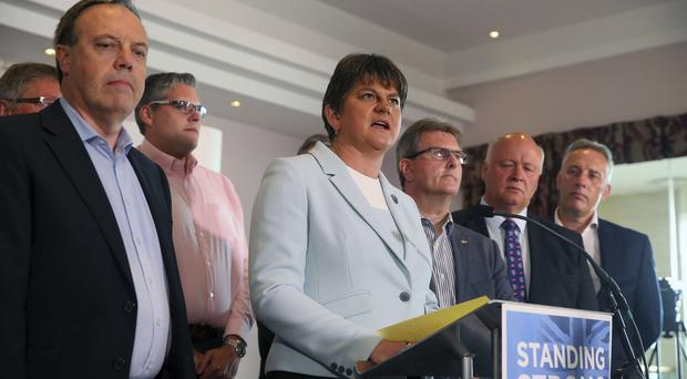 Democratic Unionist Party leader Arlene Foster, center, speaks to the media, surrounded by her party Members of Parliament, during a press conference at the Stormont hotel in Belfast (Peter Morrison/AP)
