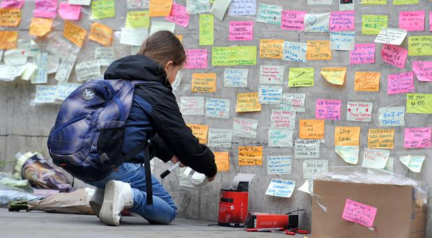 A young girl leaves a message of support on the base of the obelisk on London Bridge following the terror attack (Nick Ansell/PA)