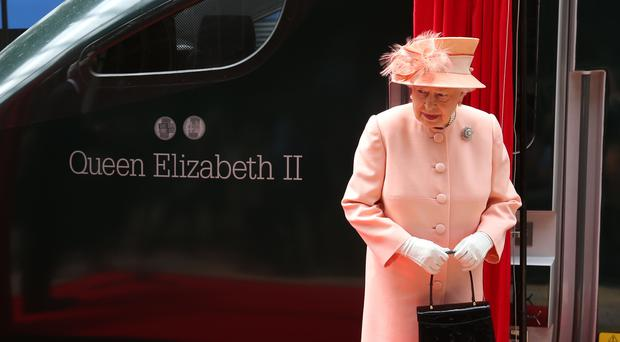 The Queen unveils the new livery of the train as she and the Duke of Edinburgh arrive at Paddington Station in London, as they marked the 175th anniversary of the first train journey by a British monarch (Jonathan Brady/PA)