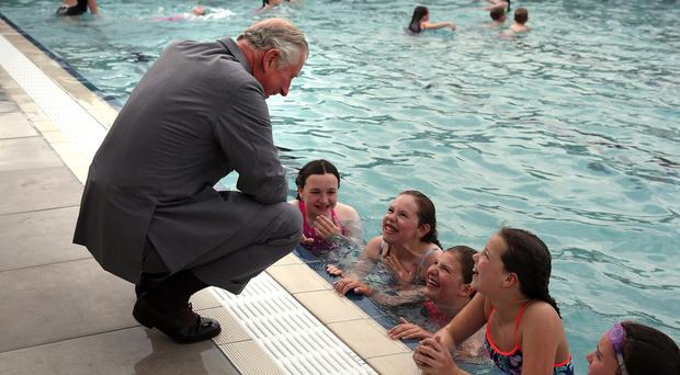 The Prince of Wales pulls his trousers up to avoid a puddle as he chats to young swimmers (Andrew Milligan/PA)