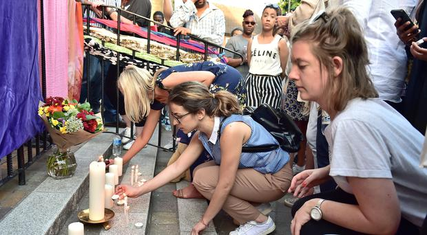 Candles are lit as people gather for prayers outside the Notting Hill Methodist Church in the shadow of the Grenfell Tower (Dominic Lipinski/PA)